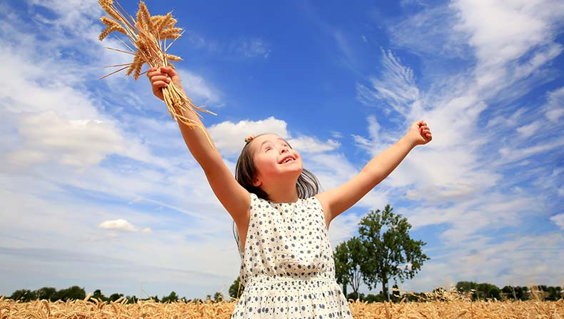 Young Girl Dancing and looking at the sky in Wheat Field