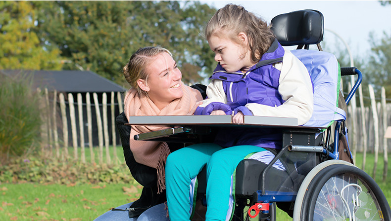 child in motorized wheelchair with smiling caregiver kneeling beside her