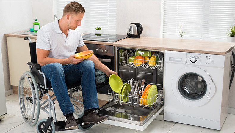 man in wheelchair loading dishwasher